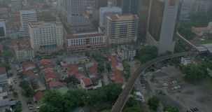 Bird eye view of poor district and riding train on railways and then up to the modern district with skyscrapers. Kuala. Overhead view of railways and train stock footage