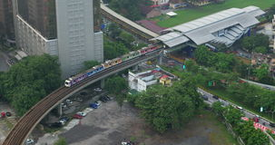 Bird eye view of railways across road against city landscape. Kuala Lumpur, Malaysia. Bird eye side view of railways crossing multilevel road against city stock footage