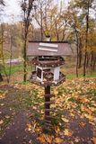 Bird feeder in the park. The tree trunk is decorated with a multi-colored striped knitted thing. stock photo