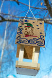 A bird feeder with a roof. On the roof of a drawn figure. The animal depicted in the cap with a curved stick, around patterns and. Snowflakes. Feeder hanging on royalty free stock photography