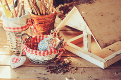 Bird feeder with seeds on wooden table in cozy country house, vintage toned Royalty Free Stock Image