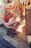Bird feeder with seeds on wooden table in cozy country house, vintage toned Stock Images