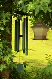 Bird feeder & Wind Chimes. A bird feeder next to some very deep toned wind chimes hanging from a tree in Royal, Arkansas Stock Image