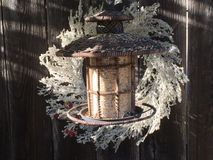 Bird feeder and wreath. In the late afternoon sun in winter near Christmas Royalty Free Stock Images