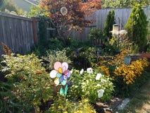 Bird feeders, plants, and yellow flowers in backyard with wood fence. Bird feeders, pinwheel, plants, and yellow flowers in backyard with wood fence royalty free stock photo