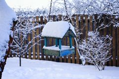 Bird feeders blue color wood fence tree garden snow light sky winter Royalty Free Stock Photo