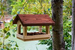 Bird feeders. Wooden racks for birds on a tree. Bird feeders in the autumn garden. Wooden racks for birds on a tree stock images