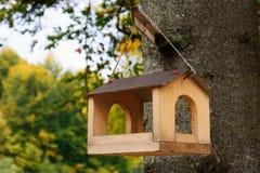 Bird feeders. Wooden racks for birds on a tree. Bird feeders in the autumn garden. Wooden racks for birds on a tree stock photos