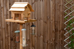 Bird Feeding Table against a wooden Fence. Bird Feeding Table with nuts and seeds hanging from it against a wooden fence with a trellis on it Stock Photography
