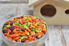 Bird food on stainless bowl and little house Royalty Free Stock Photo