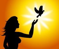 A Bird In The Hand Set Free. An illustration featuring a female silhouette with her hand raised as a bird like a dove flies away Royalty Free Stock Photo