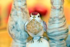 A bird having various colored plumage. At the showcase in a souvenir shop standing on between the two marble vases Royalty Free Stock Image