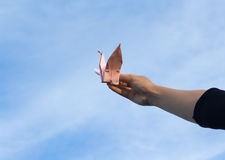 Bird. Holding paper in hand Beautiful sky backdrop Stock Photo