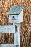 Bird House. A bird house on a fence post in front of a corn field Royalty Free Stock Image