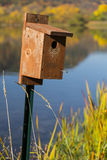 Bird House Autumn. A wooden bird house by a lake with fall colors stock images