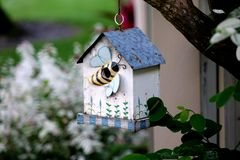 Bird house with decorative bee. A close up of a bird house with a decorative bee hanging on a tree branch stock photo