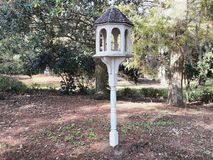 Bird House and Feeder. In the park during the fall mouths of the year. The bird house is panted white with covered shingles royalty free stock photography