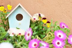 Bird house and flowers in the garden. Little bird house and flowers in the garden royalty free stock image