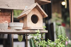 The bird house is made of natural dyed wood placed on wooden shelves. royalty free stock photo