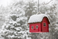 Bird house with snow in winter. Red bird house hanging outdoors in winter covered with snow royalty free stock photo