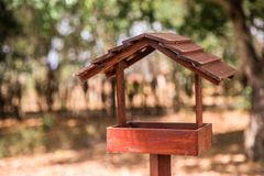 A bird house view in a farm with a calm atmosphere. Side view of a wood bird house in a farm with a blue sky and trees. Nature, rural and farm are in this stock photos