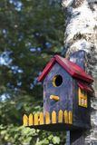 Bird house with window and fence. On birch stock images