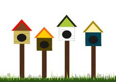 Bird houses. A few wood bird houses in the backyard, eye catching and colourful, standing on top of the grass with white tiny flowers Stock Image
