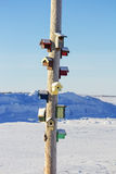 Bird houses nailed to a post. Multiple bird houses nailed to a post in front of a snow bank Royalty Free Stock Photo