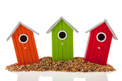 Bird houses and seed. Colorful bird houses and seed isolated over white background Stock Photography