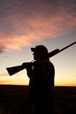 Hunter Contemplates the Day. A  bird hunter silhoutted against a dramatic sunrise with shotgun Stock Photography