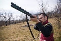 Bird hunting. Hunter with barrel aiming bird Stock Photos