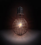Bird inside a lightbulb shaped cage Royalty Free Stock Images