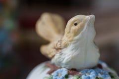 Bird on a jewlery box. Macro detail of a bird porcelaine figurine on a ceramic jewlery box stock image