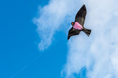 Bird kite flying in dramatic blue cloudy sky Stock Photography