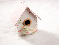 Bird in a nest fabric house with round window Stock Photo