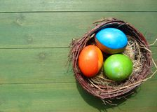 Bird nest  full of Easter eggs lying on wooden board Stock Photos