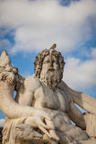 Bird perched on an ancient stone statue Stock Photos