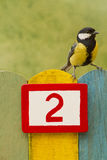 Bird perched on a fence with the number two painted on it Royalty Free Stock Images