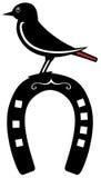 Bird perched on a horseshoe Stock Photo