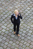 Bird's-eye view of a businesswoman in the street on the phone Royalty Free Stock Images