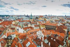 Bird`s eye view of the city of Prague with overcast sky seen from the Old Town Hall Tower, also known as the Clock Tower.  Stock Photo