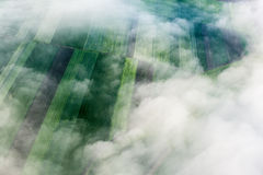 Birds eye view of the earth. Above the clouds, birds eye view of the fields and agricultural parcel Stock Image
