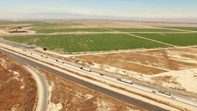 Bird's eye view of freeway traffic by agricultural farmlands stock video footage