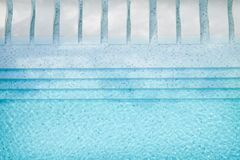 Bird`s eye view of a large swimming pool with white deck chairs royalty free stock image