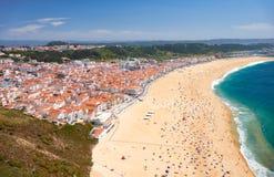 Bird`s-eye view on Nazare beach riviera on the coast of Atlantic. Ocean with Nazare town. Portugal Stock Photos