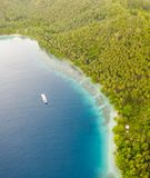 Aerial of Island, Ship, and Fringing Reef in Papua New Guinea. A bird`s eye view of the remote island of New Ireland in Papua New Guinea and a healthy fringing royalty free stock images