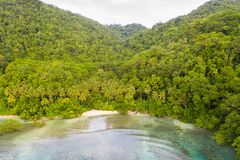 Aerial of Island Coastline and Reef in Papua New Guinea. A bird`s eye view of the remote island of New Ireland in Papua New Guinea shows a tranquil lagoon and stock photography