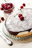 Bird`s Milk souffle cake, covered with chocolate glaze and decorated with ripe cherries royalty free stock photography