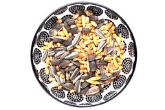 Bird seeds. Close-up of a decorative bowl with black sunflower seeds and other seed and nuts for feeding wild birds. Animal stock images