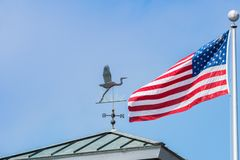 Bird shaped weather vane; the american national flag in the background, San Francisco bay area, California royalty free stock photos
